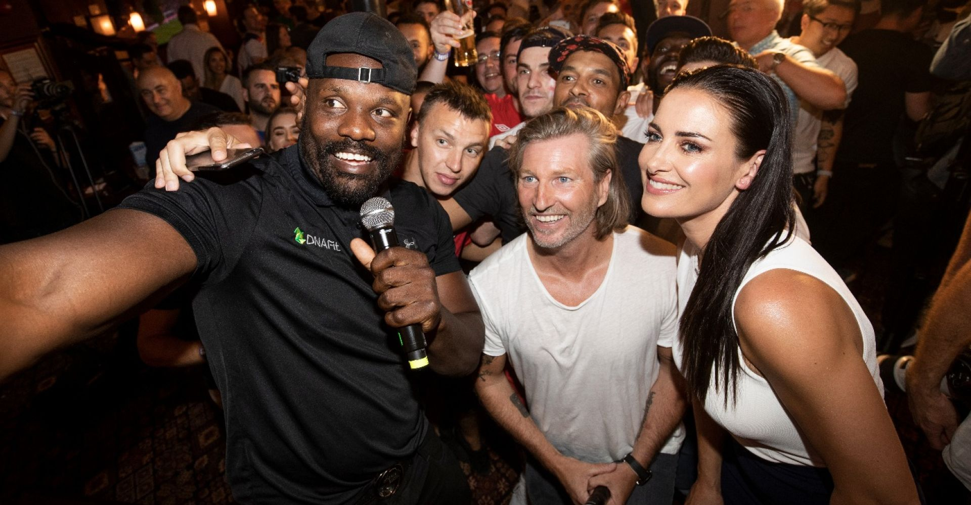 Dereck Chisora, Robbie Savage and Kirstie Gallagher take a selfie with the punters at the William Hill Arms